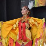 A young woman stands on a stage with her arms stretched out while wearing regalia