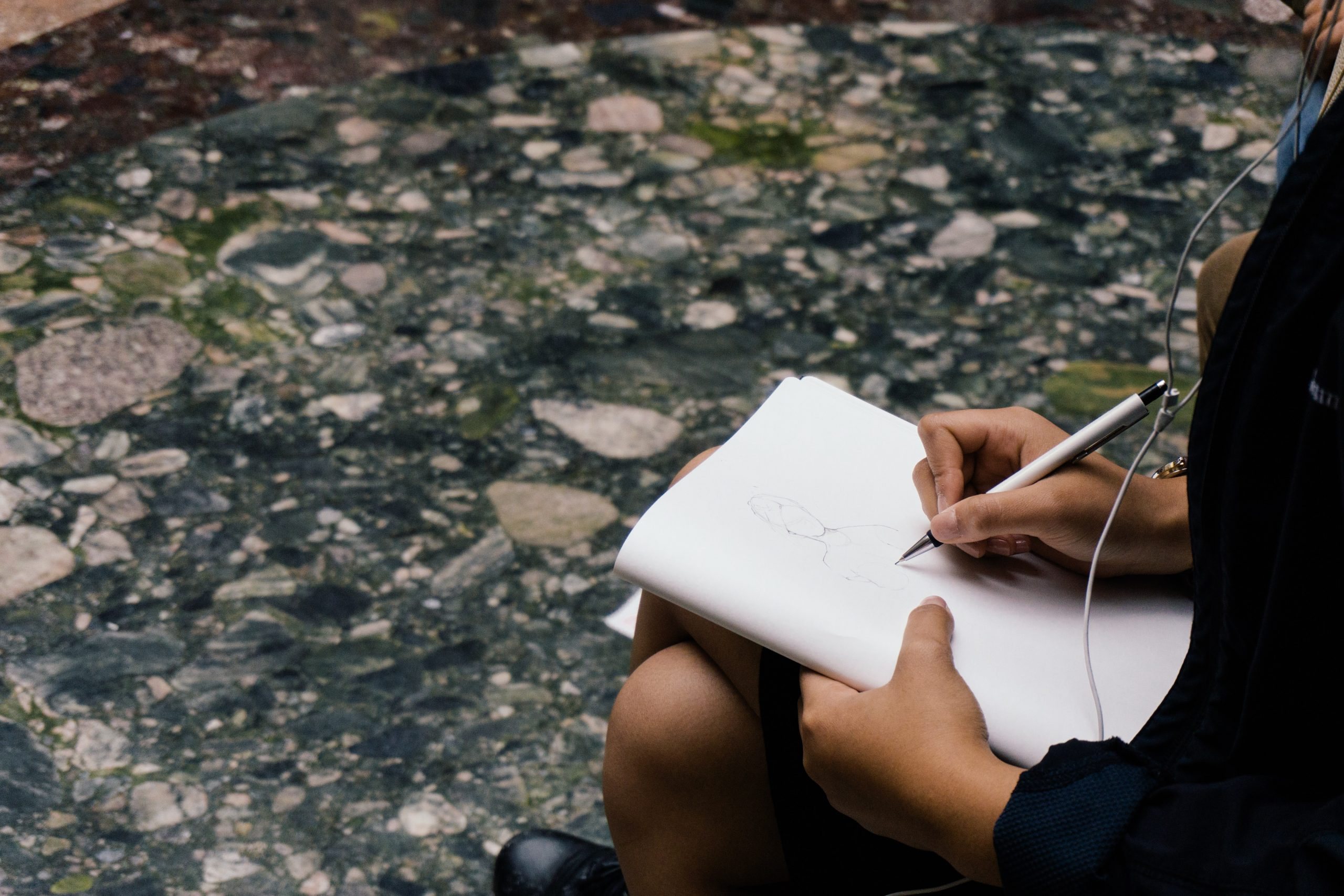 A person is outside with their hands seen drawing on a notepad